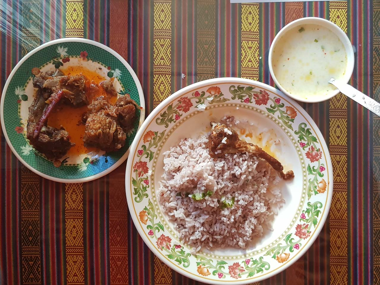 A Bhutanese meal. Top right is their datshi (creamy and cheesy iquid, sometimes with chillies, sometimes with potatoes), red rice, and meat. The meat is usually dried before anything else is done to it